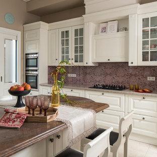 Свежая идея для дизайна: отдельная, линейная кухня в стиле современная классика с фасадами с выступающей филенкой, белыми фасадами, техникой из нержавеющей стали, островом и бежевым полом - отличное фото интерьера