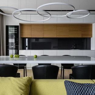 На фото: прямая кухня в современном стиле с плоскими фасадами, черным фартуком и бежевым полом