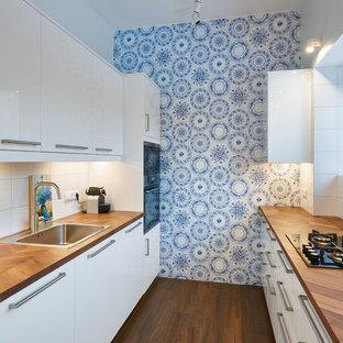 Новый формат декора квартиры: отдельная, параллельная кухня среднего размера в современном стиле с плоскими фасадами, белыми фасадами, накладной раковиной, столешницей из дерева, белым фартуком, техникой под мебельный фасад и коричневым полом