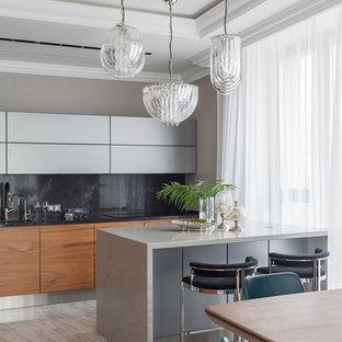 Пример оригинального дизайна интерьера: линейная кухня в современном стиле с обеденным столом, плоскими фасадами, серыми фасадами, черным фартуком, островом, серым полом и серой столешницей