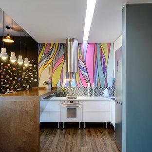 Пример оригинального дизайна интерьера: угловая кухня в современном стиле с разноцветным фартуком, полом из ламината, коричневым полом, белой столешницей, обеденным столом, плоскими фасадами, белыми фасадами, фартуком из плитки мозаики, техникой из нержавеющей стали и полуостровом