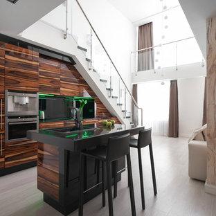 Свежая идея для дизайна: параллельная кухня-гостиная в современном стиле с накладной раковиной, плоскими фасадами, фасадами цвета дерева среднего тона, черной техникой, светлым паркетным полом и островом - отличное фото интерьера
