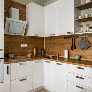 Идея дизайна: угловая кухня в современном стиле с накладной раковиной, плоскими фасадами, белыми фасадами, деревянной столешницей, коричневым фартуком, фартуком из дерева, белой техникой, коричневым полом и коричневой столешницей