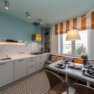 Свежая идея для дизайна: линейная кухня в современном стиле с обеденным столом, врезной раковиной, плоскими фасадами, серыми фасадами, серым фартуком, фартуком из мрамора и разноцветным полом без острова - отличное фото интерьера