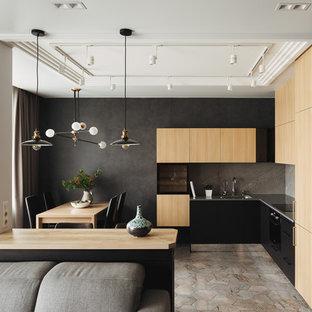 Свежая идея для дизайна: угловая кухня-гостиная в современном стиле с врезной раковиной, плоскими фасадами, черными фасадами, серым фартуком, черной техникой, черной столешницей и фартуком из каменной плиты без острова - отличное фото интерьера
