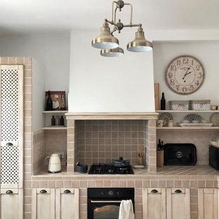 他の地域の中くらいの地中海スタイルのおしゃれなキッチン (エプロンフロントシンク、レイズドパネル扉のキャビネット、ベージュのキャビネット、タイルカウンター、ベージュキッチンパネル、磁器タイルのキッチンパネル、黒い調理設備、セラミックタイルの床、ベージュの床、ベージュのキッチンカウンター) の写真