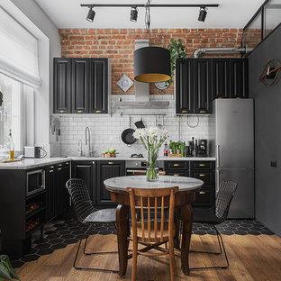 Diseño de cocina en L, industrial, abierta, sin isla, con armarios con paneles con relieve, puertas de armario negras, salpicadero blanco, salpicadero de azulejos tipo metro y electrodomésticos de acero inoxidable