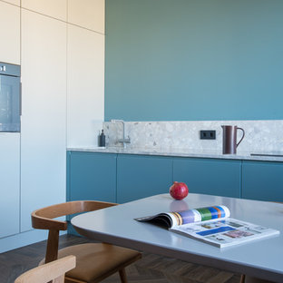 This is an example of a mid-sized contemporary single-wall kitchen in Other with flat-panel cabinets, blue cabinets, blue splashback, medium hardwood floors, no island, brown floor, grey benchtop and terrazzo benchtops.