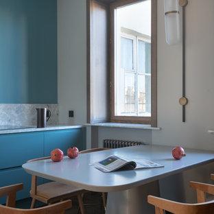 На фото: линейная кухня среднего размера в современном стиле с плоскими фасадами, синими фасадами, синим фартуком, серой столешницей и столешницей терраццо без острова с