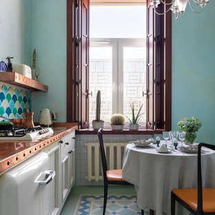 Photo of a small midcentury single-wall eat-in kitchen in Moscow with a single-bowl sink, recessed-panel cabinets, white cabinets, copper benchtops, multi-coloured splashback, ceramic splashback, white appliances, ceramic floors, multi-coloured floor and orange benchtop.