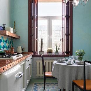 Idée de décoration pour une petite cuisine américaine linéaire vintage avec un évier 1 bac, un placard avec porte à panneau encastré, des portes de placard blanches, un plan de travail en cuivre, une crédence multicolore, une crédence en carreau de céramique, un électroménager blanc, un sol en carrelage de céramique, un sol multicolore et un plan de travail orange.