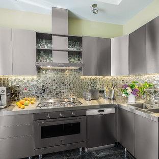 Стильный дизайн: отдельная, угловая кухня в современном стиле с двойной раковиной, плоскими фасадами, фасадами из нержавеющей стали, столешницей из нержавеющей стали, серым фартуком, техникой из нержавеющей стали и черным полом без острова - последний тренд