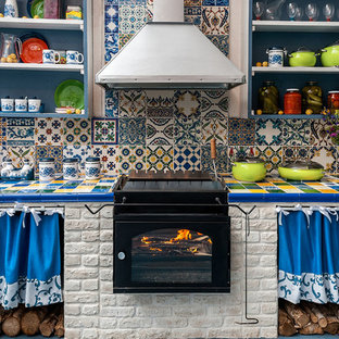 Cette photo montre une cuisine éclectique avec un placard sans porte, des portes de placard bleues, un plan de travail en carrelage, une crédence multicolore, une crédence en carreau de céramique et un électroménager noir.