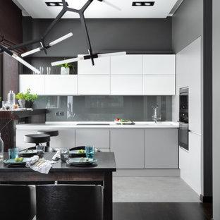 Пример оригинального дизайна: угловая кухня в современном стиле с плоскими фасадами, белыми фасадами, техникой из нержавеющей стали, серым полом и белой столешницей без острова