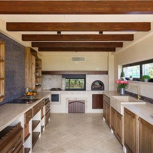 На фото: п-образная кухня в стиле кантри с раковиной в стиле кантри, фасадами цвета дерева среднего тона, бежевым полом, бежевой столешницей, фасадами с филенкой типа жалюзи и синим фартуком без острова с