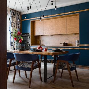 Свежая идея для дизайна: прямая кухня в современном стиле с обеденным столом, плоскими фасадами, синими фасадами, деревянной столешницей, черной техникой, паркетным полом среднего тона, коричневым полом и коричневой столешницей без острова - отличное фото интерьера