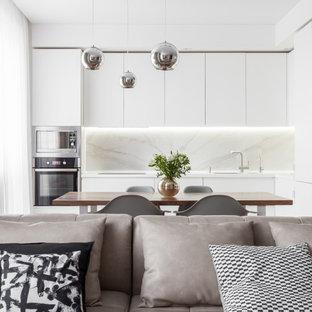 На фото: маленькая угловая кухня-гостиная в современном стиле с врезной раковиной, белыми фасадами, белым фартуком и белой столешницей без острова с