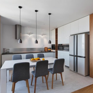 This is an example of a large contemporary l-shaped open plan kitchen in Yekaterinburg with flat-panel cabinets, white cabinets, metallic splashback, stainless steel appliances, ceramic floors, no island, grey floor, an undermount sink and metal splashback.