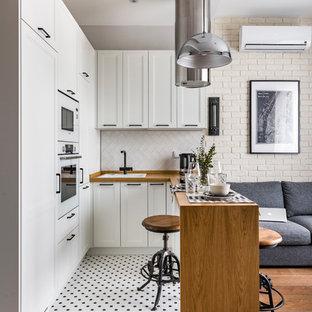 Idee per una piccola cucina contemporanea con lavello da incasso, ante con riquadro incassato, ante bianche, top in legno, paraspruzzi bianco, elettrodomestici bianchi, penisola, top marrone e pavimento multicolore