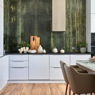 Неиссякаемый источник вдохновения для домашнего уюта: угловая кухня в современном стиле с обеденным столом, плоскими фасадами, белыми фасадами, черным фартуком, черной техникой, коричневым полом и зеленой столешницей без острова