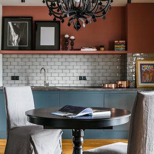 Новые идеи обустройства дома: линейная кухня-гостиная в современном стиле с накладной раковиной, плоскими фасадами, синими фасадами, серым фартуком, паркетным полом среднего тона, коричневым полом, черной техникой и серой столешницей без острова