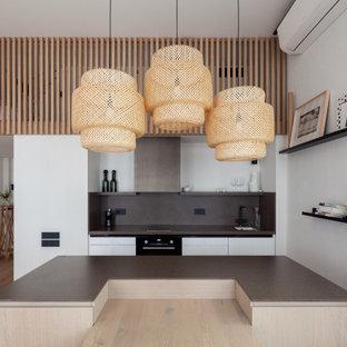 Пример оригинального дизайна: кухня-гостиная в скандинавском стиле с одинарной раковиной, плоскими фасадами, белыми фасадами, серым фартуком, светлым паркетным полом, островом, бежевым полом и серой столешницей