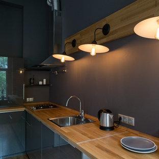 На фото: угловая кухня среднего размера в стиле лофт с обеденным столом, одинарной раковиной, плоскими фасадами, серыми фасадами, столешницей из дерева, серым фартуком, техникой из нержавеющей стали и полом из бамбука без острова с