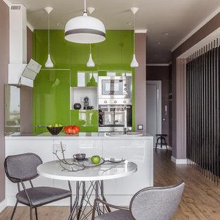 Пример оригинального дизайна: прямая кухня-гостиная в современном стиле с накладной раковиной, плоскими фасадами, зелеными фасадами, фартуком из стекла, техникой из нержавеющей стали, полом из цементной плитки, полуостровом, коричневым полом и белой столешницей