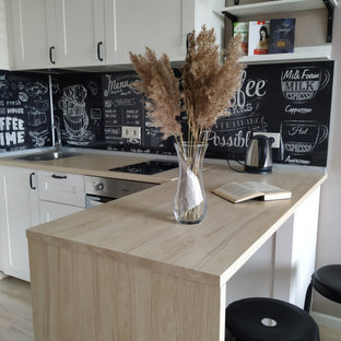 Small scandinavian single-wall open plan kitchen in Moscow with raised-panel cabinets, white cabinets, laminate benchtops, black splashback, stainless steel appliances, laminate floors, beige floor and beige benchtop.