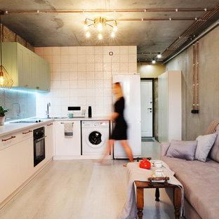 На фото: угловая кухня-гостиная в стиле лофт с накладной раковиной, плоскими фасадами, белыми фасадами, разноцветным фартуком, черной техникой, бежевым полом и серой столешницей без острова