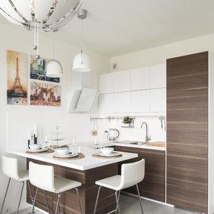 На фото: маленькая п-образная кухня-гостиная в современном стиле с накладной раковиной, плоскими фасадами, темными деревянными фасадами, полуостровом, серым полом, белой столешницей, белым фартуком, фартуком из каменной плитки и полом из ламината с