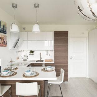 サンクトペテルブルクの中くらいの北欧スタイルのおしゃれなキッチン (ドロップインシンク、フラットパネル扉のキャビネット、濃色木目調キャビネット、白いキッチンパネル、グレーの床、白いキッチンカウンター、クオーツストーンカウンター、石スラブのキッチンパネル、ラミネートの床) の写真