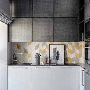 На фото: угловые кухни в современном стиле с накладной раковиной, плоскими фасадами, разноцветным фартуком, техникой из нержавеющей стали, серым полом, серой столешницей и серыми фасадами