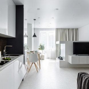 Идея дизайна: маленькая прямая кухня-гостиная в современном стиле с белым полом, врезной раковиной, плоскими фасадами, коричневым фартуком, фартуком из стекла, серой столешницей, столешницей из ламината и черно-белыми фасадами без острова