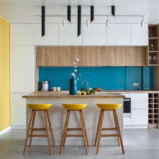 На фото: прямая кухня в современном стиле с накладной раковиной, плоскими фасадами, белыми фасадами, деревянной столешницей, синим фартуком, фартуком из стекла, техникой из нержавеющей стали, островом, серым полом и коричневой столешницей