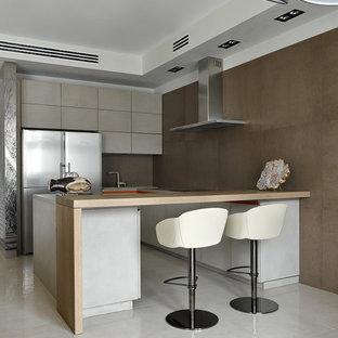 Выдающиеся фото от архитекторов и дизайнеров интерьера: п-образная кухня-гостиная в современном стиле с плоскими фасадами, коричневым фартуком, техникой из нержавеющей стали, серыми фасадами и полуостровом