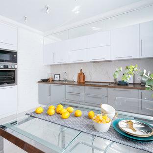 Пример оригинального дизайна: угловая кухня среднего размера в современном стиле с накладной раковиной, плоскими фасадами, белыми фасадами, столешницей из ламината, белым фартуком, фартуком из керамогранитной плитки, техникой из нержавеющей стали, полом из керамогранита, белым полом, коричневой столешницей и обеденным столом без острова
