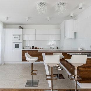 Новые идеи обустройства дома: п-образная кухня-гостиная в современном стиле с плоскими фасадами, фасадами цвета дерева среднего тона, белым фартуком, белой техникой, белым полом и белой столешницей