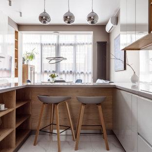 Источник вдохновения для домашнего уюта: п-образная кухня-гостиная в современном стиле с плоскими фасадами, серыми фасадами, белым фартуком, полуостровом, белым полом и серой столешницей