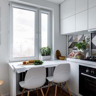 Стильный дизайн: отдельная кухня в скандинавском стиле с плоскими фасадами, белыми фасадами, разноцветным фартуком, черной техникой и белой столешницей - последний тренд