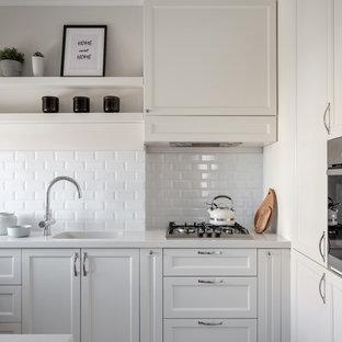 На фото: кухни в современном стиле с монолитной раковиной, фасадами с утопленной филенкой, белыми фасадами, белым фартуком, фартуком из плитки кабанчик, техникой из нержавеющей стали и белой столешницей