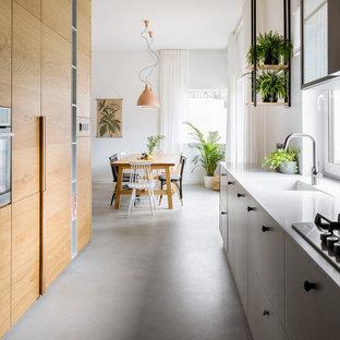 Пример оригинального дизайна: параллельная кухня в современном стиле с монолитной раковиной, плоскими фасадами, фасадами цвета дерева среднего тона, бетонным полом, серым полом и белой столешницей без острова