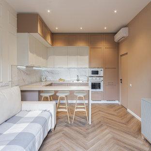 Идея дизайна: угловая кухня-гостиная в современном стиле с фасадами в стиле шейкер, бежевыми фасадами, белым фартуком, белой техникой, полуостровом, бежевым полом и белой столешницей