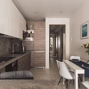 Создайте стильный интерьер: линейная кухня-гостиная в современном стиле с одинарной раковиной, плоскими фасадами, фасадами цвета дерева среднего тона, коричневым фартуком, серым полом и черной техникой - последний тренд