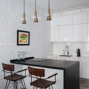 Выдающиеся фото от архитекторов и дизайнеров интерьера: параллельная кухня-гостиная в современном стиле с врезной раковиной, плоскими фасадами, белыми фасадами, белым фартуком, полуостровом, серым полом, черной столешницей, техникой под мебельный фасад и паркетным полом среднего тона