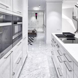 Пример оригинального дизайна: параллельная кухня-гостиная в современном стиле с плоскими фасадами, белыми фасадами, черной техникой, островом и белым полом