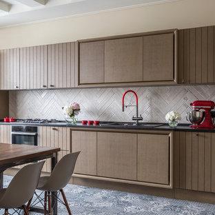 Свежая идея для дизайна: линейная кухня-гостиная среднего размера в современном стиле с накладной раковиной, плоскими фасадами, коричневыми фасадами, серым фартуком, черной техникой и разноцветным полом без острова - отличное фото интерьера