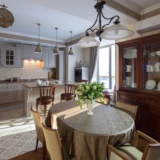 На фото: угловая кухня - столовая в классическом стиле с фасадами с утопленной филенкой, серыми фасадами, бежевым фартуком, островом и серым полом с