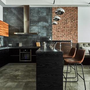 Неиссякаемый источник вдохновения для домашнего уюта: п-образная кухня-гостиная в стиле лофт с плоскими фасадами, черными фасадами, серым фартуком, техникой из нержавеющей стали, полуостровом, серым полом и черной столешницей