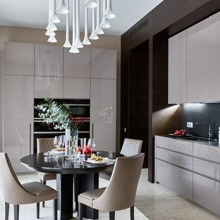 Свежая идея для дизайна: кухня в современном стиле с обеденным столом, врезной раковиной, плоскими фасадами, бежевыми фасадами, столешницей из гранита, черным фартуком, черной техникой, полом из травертина и бежевым полом без острова - отличное фото интерьера